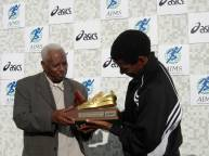 Dr Woldmeskel Kostrea presents AIMS/ASICS Golden Shoe Award to Haile Gebrselassie.